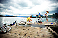 JEROME A. POLLOS/Press..Johnny Haines, left, and Levi Harvey change out their fishing lures as Cierra Harvey helps Dakota Ray, right, bring in a small fish at the Honeysuckle Beach dock in Hayden. The fishing party took to their bikes to enjoy Wednesday afternoon reeling in fish in the cool weather and under cloudy skies that have been absent to the area for weeks.