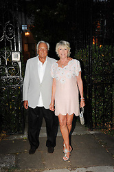 MICHAEL WINNER and GERALDINE LYNTON-EDWARDS  leaving a summer party hosted by Lady Annabel Goldsmith at her home Ormeley Lodge, Ham Gate, Richmond on 13th July 2010.