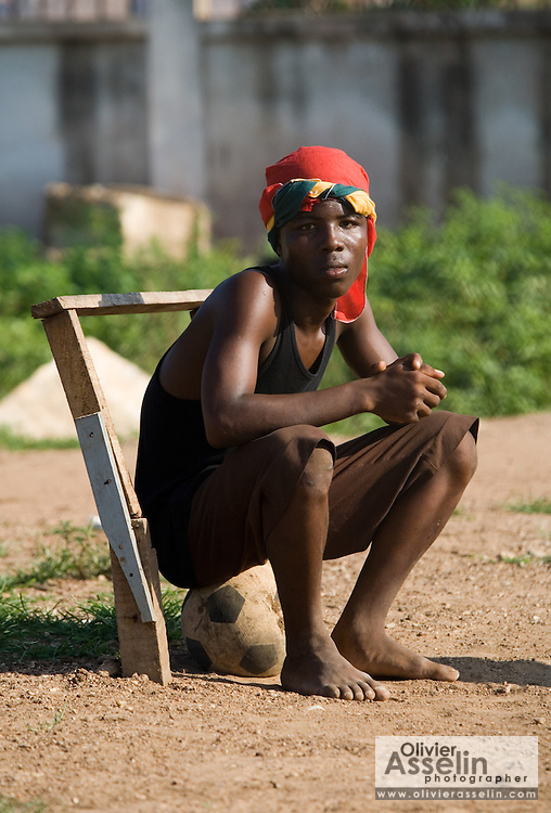 Boy sitting on football in Accra, Ghana, 2006.