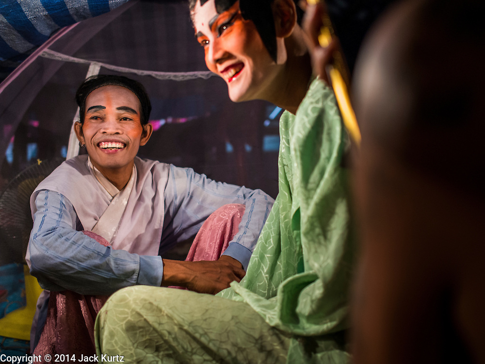 "18 AUGUST 2014 - BANGKOK, THAILAND:   Members of the Lehigh Leng Kaitoung Opera troupe share a beer backstage before a performance at Chaomae Thapthim Shrine, a small Chinese shrine in a working class neighborhood of Bangkok. The performance was for Ghost Month. Chinese opera was once very popular in Thailand, where it is called ""Ngiew."" It is usually performed in the Teochew language. Millions of Chinese emigrated to Thailand (then Siam) in the 18th and 19th centuries and brought their culture with them. Recently the popularity of ngiew has faded as people turn to performances of opera on DVD or movies. There are still as many 30 Chinese opera troupes left in Bangkok and its environs. They are especially busy during Chinese New Year and Chinese holiday when they travel from Chinese temple to Chinese temple performing on stages they put up in streets near the temple, sometimes sleeping on hammocks they sling under their stage. Most of the Chinese operas from Bangkok travel to Malaysia for Ghost Month, leaving just a few to perform in Bangkok.     PHOTO BY JACK KURTZ"