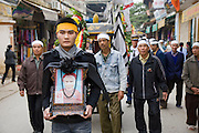 A man leading a funeral procession carries a picture of his grandmother, Trieu Thi Chat, who died at the age of 95 in Van Phuc Village, near Hanoi, Vietnam.