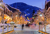 Visitors stroll the pedestrian mall of Whistler Village on a winter evening. Whistler Mountain rises behind as the lights of the village sparkle on the shop fronts. Whistler, BC, Canada
