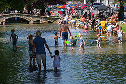 © Licensed to London News Pictures 25/06/2020, Bourton on the Water, UK. People enjoy the sun, paddle in the River Windrush and relax in the shade as the continuing good weather brings people outside wuitrh the easing of lockdown restrictions due to Covid-19. Photo Credit : Stephen Shepherd/LNP
