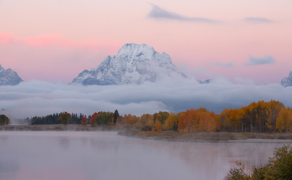 After an early season winter storm, the sun rises at Oxbow Bend to reveal Mount Moran covered in a dusting of fresh snow.