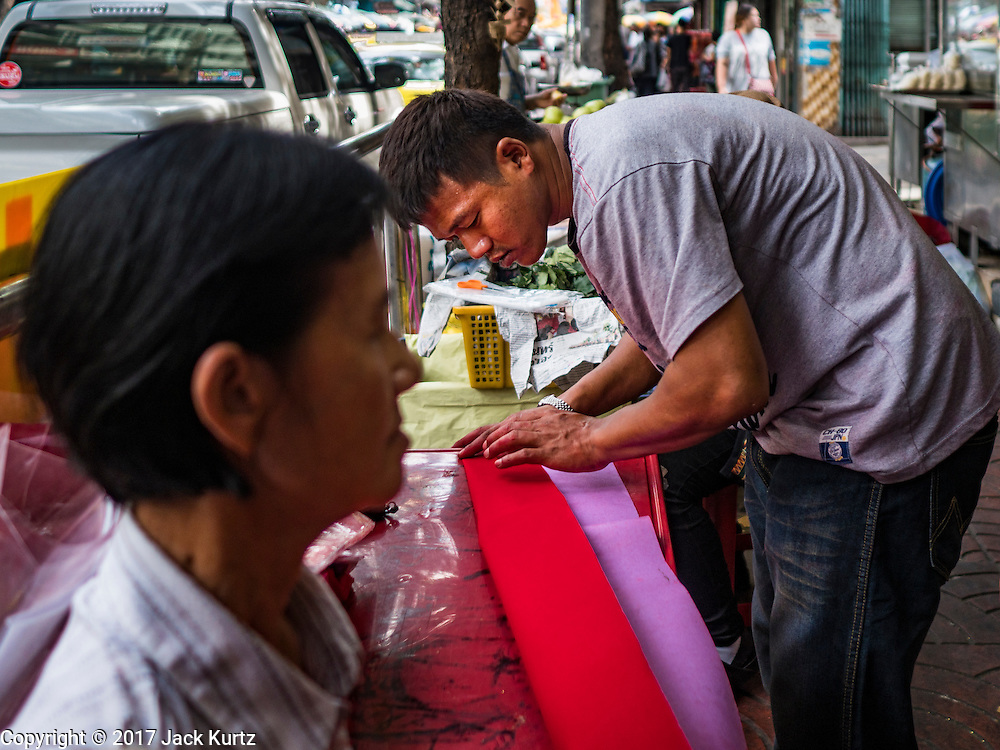 """18 JANUARY 2017 - BANGKOK, THAILAND: A man cuts red paper that a traditional Chinese calligrapher uses to draw New Years greetings in Bangkok's Chinatown district, before the celebration of the Lunar New Year. Chinese New Year, also called Lunar New Year or Tet (in Vietnamese communities) starts Saturday, 28 January. The coming year will be the """"Year of the Rooster."""" Thailand has the largest overseas Chinese population in the world; about 14 percent of Thais are of Chinese ancestry and some Chinese holidays, especially Chinese New Year, are widely celebrated in Thailand.      PHOTO BY JACK KURTZ"""