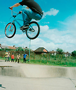 Teenager on a BMX doing a trick in the air motion