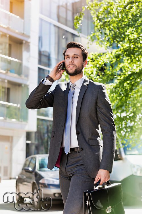 Portrait of young attractive businessman walking while talking on smartphone