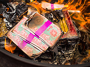"10 AUGUST 2014 - BANGKOK, THAILAND: A stack of Hell Money in a burn barrel in Bangkok on the first day of Ghost Month. Hell money is a form of joss paper printed to resemble legal tender bank notes and is used in religious ceremonies in Chinese communities. The seventh month of the Chinese Lunar calendar is called ""Ghost Month"" during which ghosts and spirits, including those of the deceased ancestors, come out from the lower realm. It is common for Chinese people to make merit during the month by burning ""hell money"" and presenting food to the ghosts.    PHOTO BY JACK KURTZ"