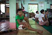 A boy waits for his mother to meet with a doctor at a mobile clinic in East Dagon township.