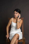 brunet model with a white dress on cell phone, black background