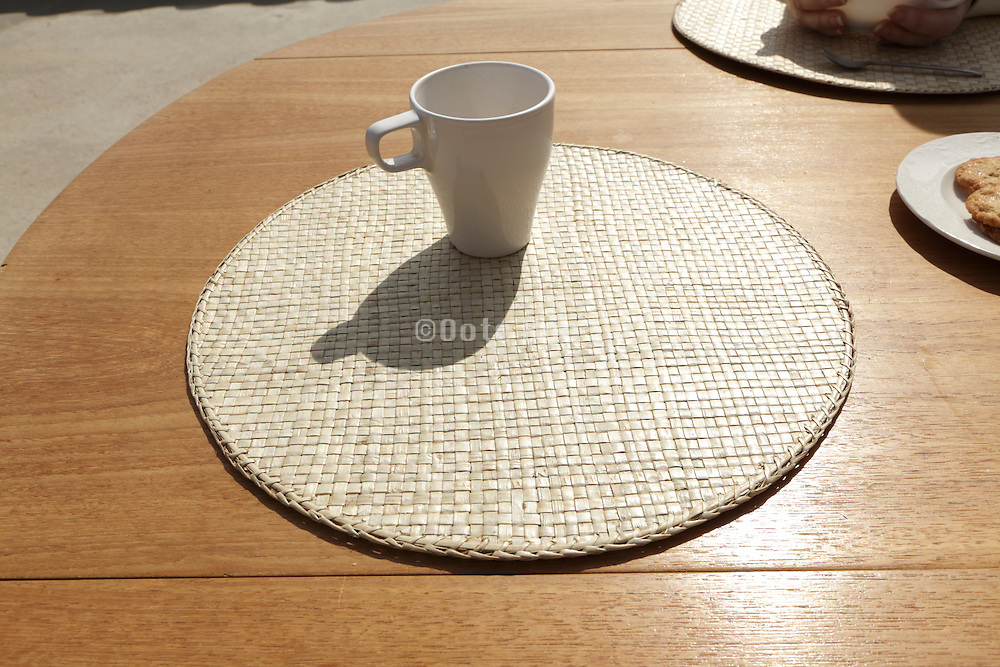 place mat with cup, cookies and hands of an second person