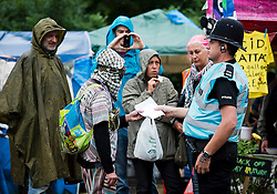 © London News Pictures. 17/08/2013. Balcombe, UK. Campaigners talk to a police officer at the entrance to the Cuadrilla drilling site in Balcombe, West Sussex which has been earmarked for fracking. Cuadrilla has temporarily ceased drilling at the site under advice from the police after campaign group No Dash For Gas threatened a weekend of civil disobedience. Photo credit: Ben Cawthra/LNP