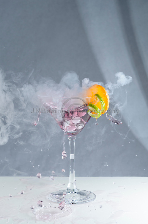 Splashing, smoky craft cocktail with fruit
