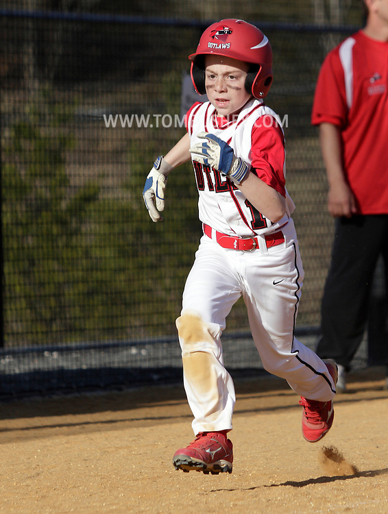 Chester, New York  - A baserunner races to home plate during  the TRUMP March Madness youth baseball tournament at The Rock Sports Park on March 17, 2012. ©Tom Bushey / The Image Works