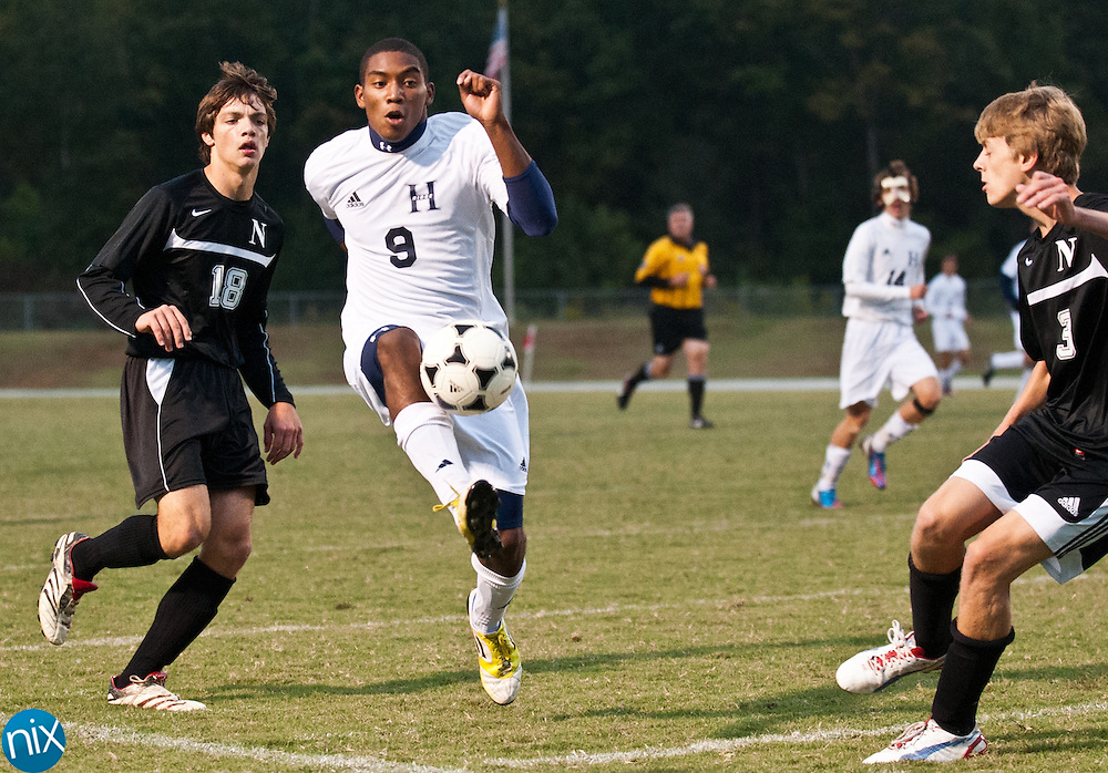 Hickory Ridge's Dryce Norales (9) tries to get the ball past Northwest Cabarrus' Noah Malina (18) and Chase Bradner (3) Monday night in Harrisburg. (Photo by James Nix)