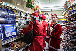 © Licensed to London News Pictures. 10/12/2016. London, UK. Revellers buy drinks in a newsagent as  thousands of Santas descend on central London for the annual drink-heavy Santacon Parade. Photo credit: Rob Pinney/LNP