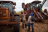 ITUMBIARA, BRAZIL - OCTOBER 16:<br /> Sugarcane field workers get ready for their shift near a tractor for pulling cut cane, left and a harvester, for cutting sugarcane stalks, near the city of Itumbiara, in Goias state, Brazil, on Wednesday, Oct. 16, 2013. Since the US recently passed a number of regulations and standards for cars and dropped tariffs that were in place for decades against Brazilian sugar, Brazilian ethanol is now flowing to the U.S., and the ethanol industry in the country is consolidating and ramping up for a new era.
