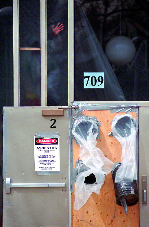 A worker seals the entrance to a high school in preparation for asbestos removal