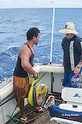 deck hand Patrick and angler Tony boating a mahi mahi, dorado, or dolphinfish, Coryphaena hippurus,  aboard Reel Addiction, based at Ika Lahi Fishing Lodge, Hunga Island, Vava'u, Kingdom of Tonga, South Pacific