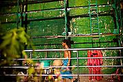 Ein Mann in blauem Longyi vor einer gruennen Wand. Yangon, Myanmar, 12ter Mai 2013.