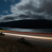 A full moon shines over Crystal Springs reservoir as cars zip along the road connecting Highway 92 to Interstate 280 and coastal fog moves in over the peninsula. San Mateo County, CA