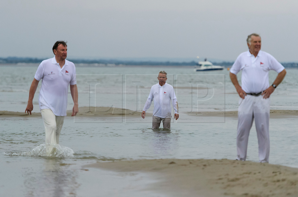 © Licensed to London News Pictures. 18/09/2016. Portsmouth, UK. Players in the field stood in water. Teams take part in the  Bramble Bank Cricket Match in the middle of The Solent strait on September 18, 2016. The annual cricket match between the Royal Southern Yacht Club and The Island Sailing Club, takes place on a sandbank which appears for 30 minutes at lowest tide. The game lasts until the tide returns. Photo credit: Ben Cawthra/LNP