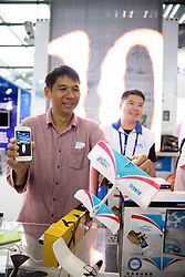 Man with cell phone operated remote control airplane at Shenzhen Hi Tech Fair 2016.