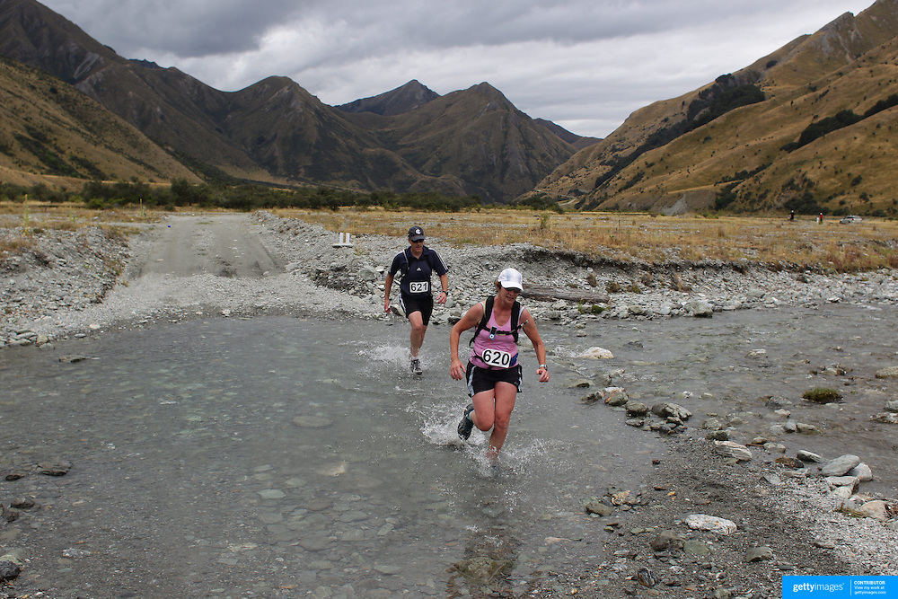 Runners Tim Bradford and Bev Bradford cross Moke Creek on the Ben Lomond High Country Station during the Pure South Shotover Moonlight Mountain Marathon and trail runs. Moke Lake, Queenstown, New Zealand. 4th February 2012. Photo Tim Clayton