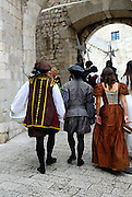 Two men and one woman, backs to camera, dressed in period costume, walking the paved streets of Dubrovnik old town, Croatia