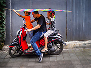 01 AUGUST 2017 - UBUD, BALI, INDONESIA: A family in Ubud carries their contemporary kite to a kite flying ground in Ubud. Kite flying is a popular past time on Bali. It originally had religious connotations, it was used to ask the gods for bountiful rains and harvests. The kites are large. Small ones, flown by individuals are about two meters long, larger ones flown by teams of up to 80 people are ten meters long. There are three shapes of traditional kites, bebean (fish-shaped), janggan (bird-shaped) and pecukan (leaf-shaped). The pecukan is the most unstable and difficult to fly.    PHOTO BY JACK KURTZ