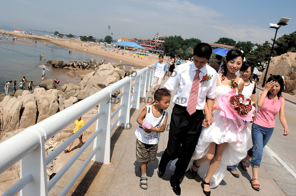 Beidaihe on the Bohai Sea 280 kilometers east of Beijing, is North China's most famous seaside resort. Every year from June to September some five million tourists, mostly Chinese but including foreign, some who live in China but host of them from eastern Russia, pass through for sun and sand. Crowds walk or drive hired bicycle along the main streets and the promenade. Heading to the sea, while there is space on roped-off, private beaches, several of them restricted to guests of adjacent hotels, the public beach is packed. People in outsize trunks and frilly one-piece costumes, beach-goers bounced over waves on airbeds and inner tubes, or just splashed in the cooling water. Beidaihe once was a famous resort for Chinese leadership. It was the former summer home of Lin Biao, the army leader who died in mysterious circumstances in 1971 after apparently trying to stage a coup against Chairman Mao Zedong. Beidaihe's resurgence began again after Deng took control of China in 1978, since than China's senior leaders slip away to Beidaihe on the Bohai coast to escape the heat of Beijing and plot strategy for the coming year. Still now there are houses of important Chinese party leader, but since Mr. Hu gained the power it's not anymore the place were the leaders use to met each other informal.  *** Local Caption *** A bride and his bridegroom walk along the promenade with some of their guests.