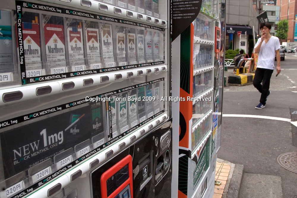 """These are Marlboro cigarettes being sold in vending machines on the streets of Tokyo. Many of these views show promotions for """"Marlboro One Black Menthol"""", the new brand of smokes that contains only 1 MG of nicotine. This American brand is distributed in Japan through Philip Morris International (PMI) which In May 2005 ended it's 32 year license agreement with Japan Tobacco Inc. to sell the Marlboro brand in Japan. Currently there are some 30 million smokers in Japan and Marlboro is one of the top selling brands. The legal smoking age in Japan is age twenty and in order to purchase smokes from these vending machines, customers must use an age verification Taspo"""" card (short for tobacco passport)..."""
