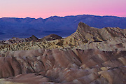 sunrise at zabriskie point, frozen fingers on the camera trigger  are ignored once the sun rises and presents a beautiful magenta sky at death valley national park in nevada