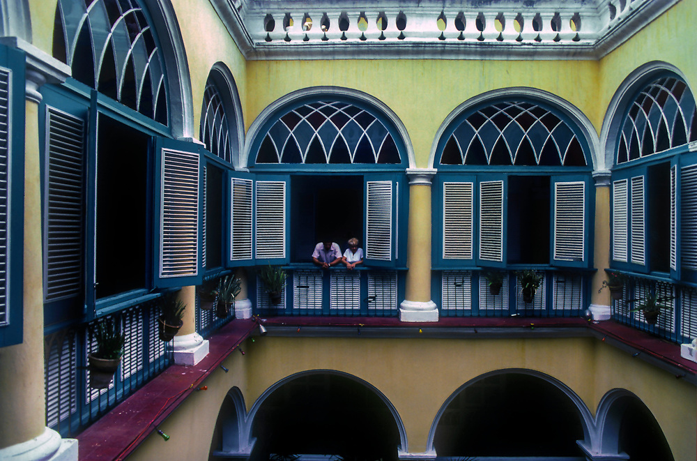 Inner courtyard of old Spanish Colonial building surrounded by stained glass windows.