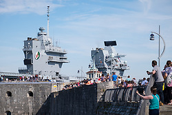 © Licensed to London News Pictures. 23/06/2018. Portsmouth, UK.  Crowds of people watching and waving as the Royal Navy's flagship, HMS Queen Elizabeth, sails into Her Majesty's Naval Base (HMNB) Portsmouth this morning, 23rd June 2018.  The aircraft carrier has been performing trials in the Northern Atlantic, including her first replenishment at sea. She is expected to remain in Portsmouth ahead of aircraft trials off the coast of the United States later this summer.Photo credit: Rob Arnold/LNP