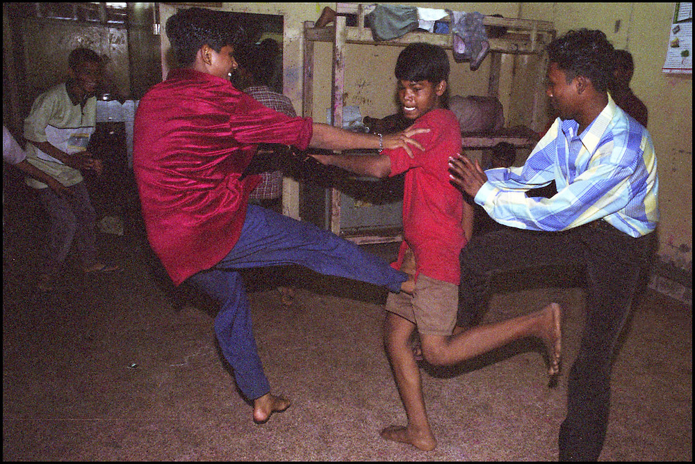 INDIA. Mumbai (Bombay). 2002. Homeless youth play fight inside the shelter.