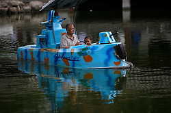 epa03265901 A Chinese man and child ride a leisure boat in a park in Beijing, China, 15 June 2012. China's one-child policy has come under scrutiny after reports circulated online of local family planning staff in Ankang city of the northern province of Shaanxi, forcibly aborted the child of a woman who was seven months pregnant. Since China's family-planning policy was introduced in 1978, many local officials have enforced abortions and sterilizations in a bid to ensure that most families have only one child.  EPA/HOW HWEE YOUNG