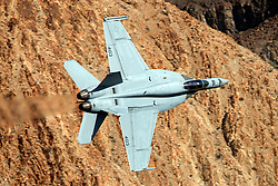 United States Navy Boeing F/A-18E Super Hornet (AG 403) from the VFA-25 Fist of the Fleet squadron Naval Air Station Lemoore, flies low level on the Jedi Transition through Star Wars Canyon / Rainbow Canyon, Death Valley National Park, Panamint Springs, California, United States of America