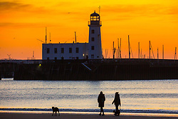 © Licensed to London News Pictures. 02/04/2020. Scarborough UK. People walk along Scarborough beach this morning as the sky is turned a golden yellow at dawn in Scarborough on the Yorkshire coast. Photo credit: Andrew McCaren/LNP