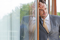 Thoughtful businessman looking away while leaning on glass door