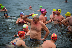 © Licensed to London News Pictures. 25/12/2016. London, UK. Swimmers at the end of the race. Members of the Serpentine Swimming Club brave the cold waters at the Serpentine Lake in Hyde Park, London to compete for the traditional Peter Pan Cup on Christmas Day, December 25, 2016. Photo credit: Ben Cawthra/LNP