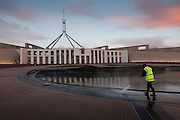 Australian Parliment House Canberra. Australian Parliament House at dawn with Canberra Queenbeyan Cleaning Services working on the entrance pond. ( name of worker not given to me) did not mind to be photographed as long a not a close-up but would not give name.
