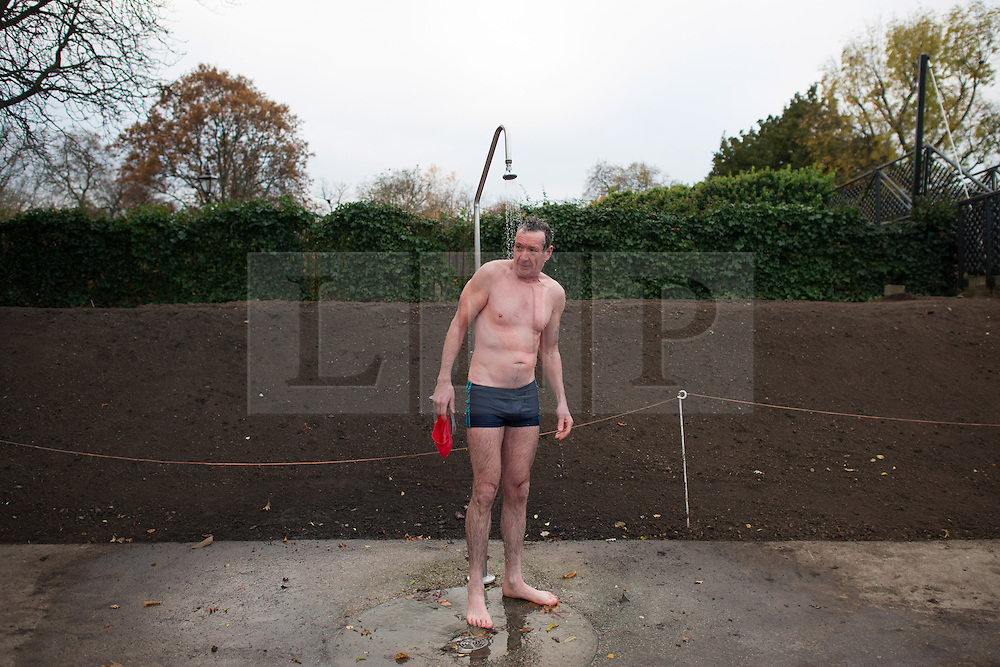 © Licensed to London News Pictures.30/11/2013. London, UK. A competitor stands under the shower after the Serpentine Swimming Club's winter swimming competition in the cold water of the Serpentine Lake in Hyde Park.Photo credit : Peter Kollanyi/LNP
