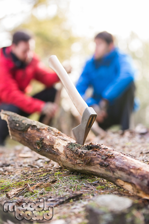 Axe stuck in log with male hikers in background at forest
