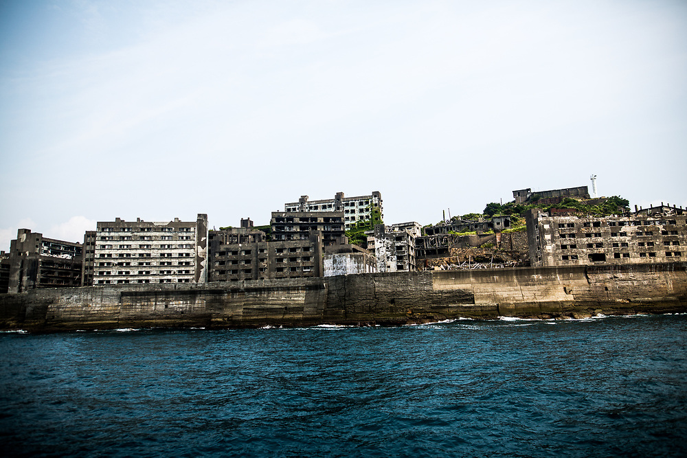 """NAGASAKI, JAPAN - AUGUST 8: Hashima Island, commonly known as Gunkanjima or """"Battleship Island"""" in Nagasaki Prefecture, southern Japan on August 8, 2017. The island was a coal mining facility until its closure in 1974 is a symbol of the rapid industrialization of Japan, a reminder of its dark history as a site of forced labor during the Second World War. The island now is recognized as UNESCO's World Heritage sites of Japan's Meiji Industrial Revolution. (Photo: Richard Atrero de Guzman/NURPhoto)"""