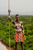 Kara tribe man with elaborate chalk painting on his body, with the Omo River behind, Dus, Omo Valley, Ethiopia.