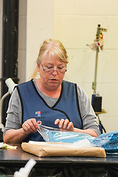 © Licensed to London News Pictures. 21/04/2020. Dukinfield, UK.   A woman folds medical clothing as staff at Tibard begin working around the clock an order of 5,000 units of nurses uniforms (scrubs) for NHS workers per week in Dukinfield , owing to growing demand during the COVID-19 pandemic. The factory typically manufactures uniforms for the catering industry.  Photo credit: Ioannis Alexopoulos /LNPP