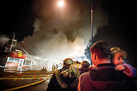 JEROME A. POLLOS/Press..Grace Robbins, 3, peers over the should of her father, Kelly Robbins, at the crowds watching a fire consume businesses and apartments Sunday night at Sherman Avenue and 12th Street in Coeur d'Alene.