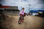 A child rides a bicycle on the way from school in Datoa village. After the RKK started targeting school children the situation changed dramatically for the population. Thailand is struggling to keep up appearances as the land of smiles has to face up to its troubled south. Since 2004 more than 3500 people have been killed and 4000 wounded in a war we never hear about. In the early hours of January 4th 2004 more than 50 armed men stormed a army weapons depot in Narathiwat taking assault rifles, machine guns, rocket launchers, pistols, rocket-propelled grenades and other ammunition. Arsonists simultaneously attacked 20 schools and three police posts elsewhere in Narathiwat. The raid marked the start of the deadliest period of armed conflict in the century-long insurgency. Despite some 30,000 Thai troops being deployed in the region, the shootings, grenade attacks and car bombings happen almost daily, with 90 per cent of those killed being civilians. 24.09.07. Photo: Christopher Olssøn.