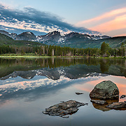 The water is perfectly still at Sprague Lake just before sunrise in Rocky Mountain National Park, Colorado.